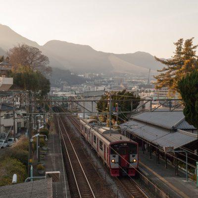 別府の市街地を背景に。近未来的な電車と一世紀以上前の駅舎とのコラボレーション。