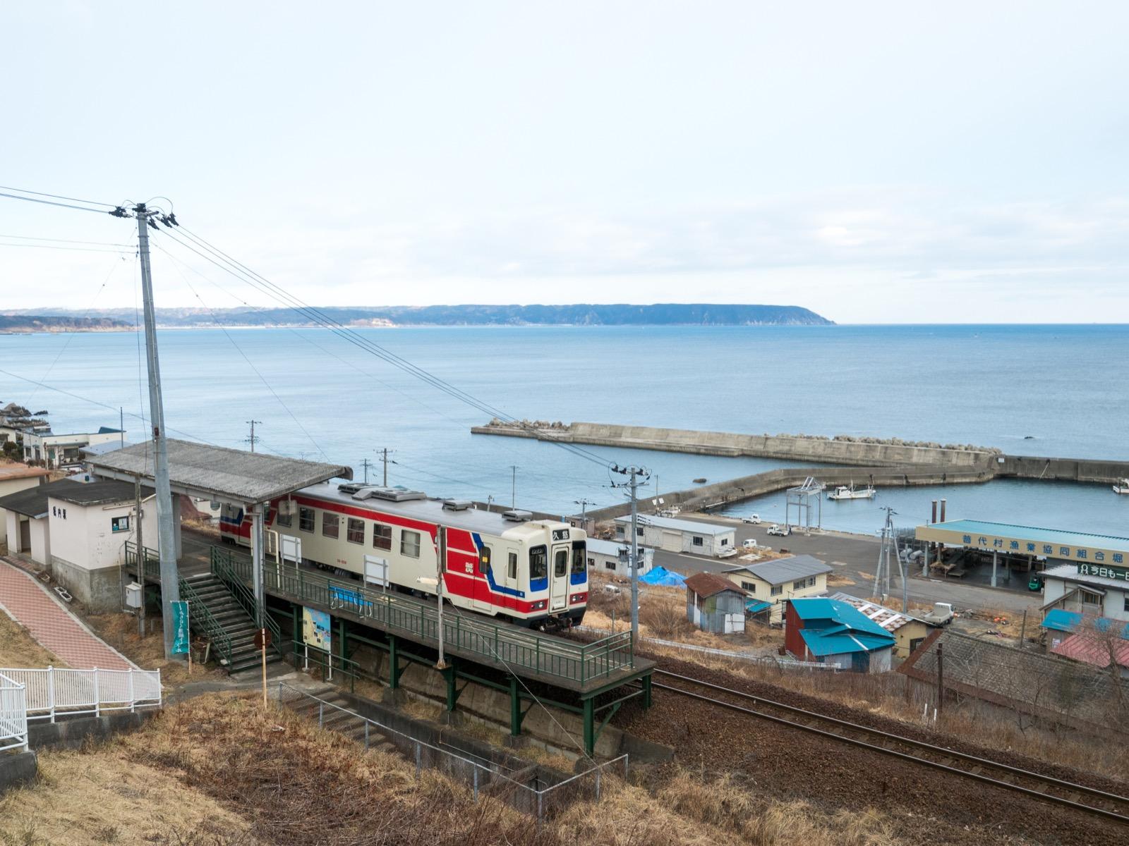 列車がやってくると、実に画になります。奥に見えるのは、野田湾の対岸にある半島のように突き出た地域。夫婦岩などがある小袖海岸は、この半島の裏にあります。