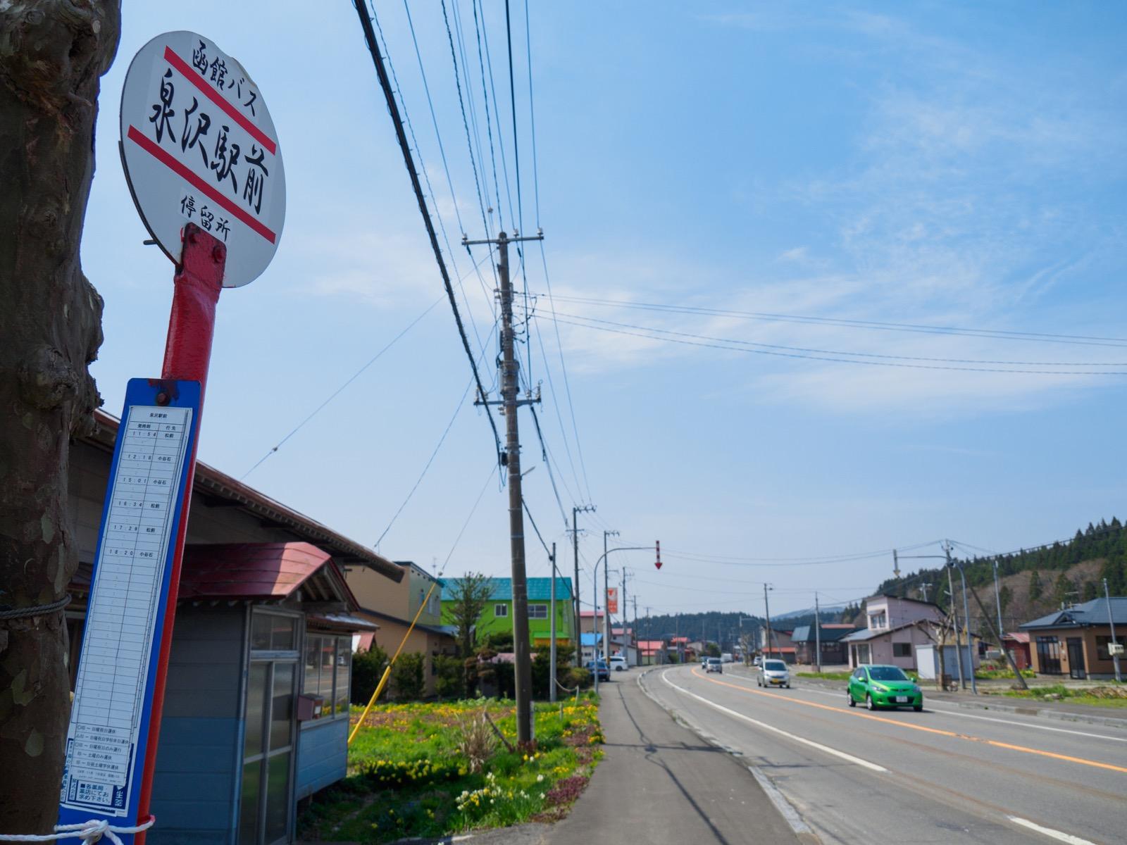 泉沢駅前を通る国道228号線と、函館バスの「泉沢駅前」バス停
