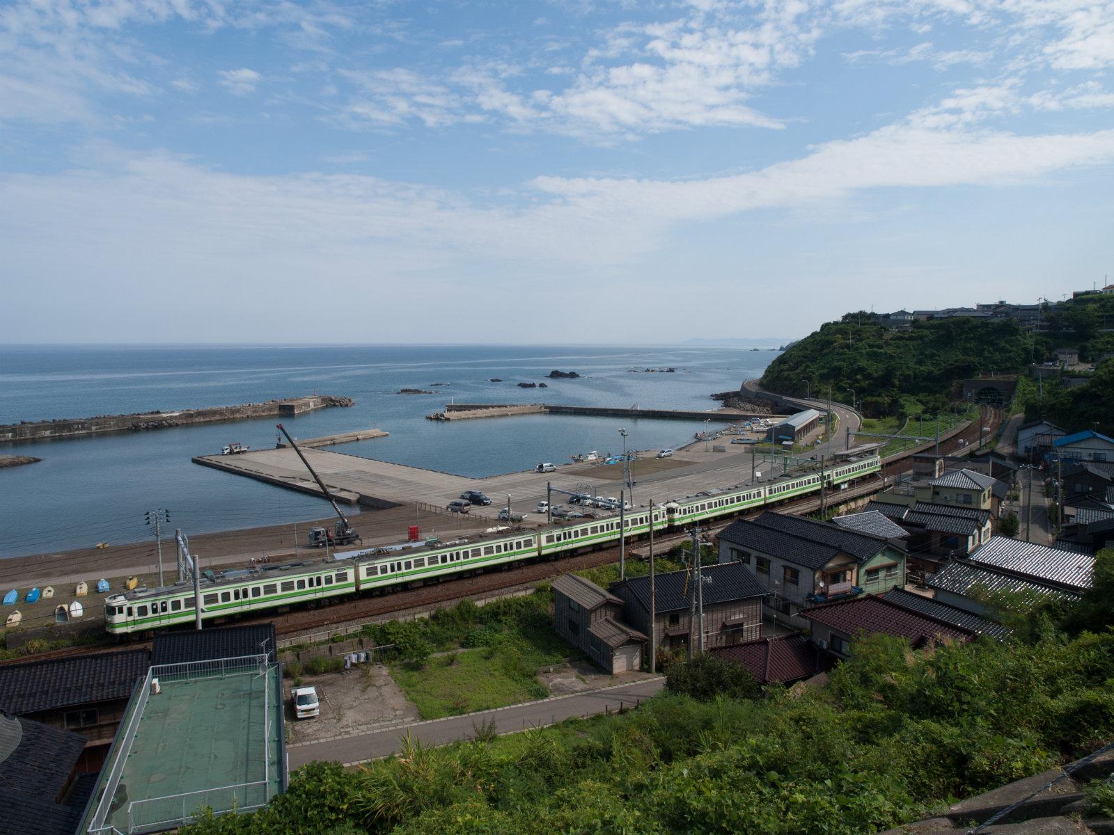 列車がゆっくりとやってきました。海と青空の前ではとても小さく見えました。