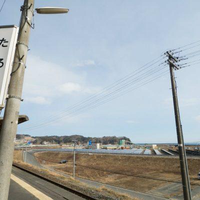 写真左半分にある白く横に伸びる建造物が防潮堤の一部です。