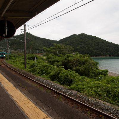 海面の色によく似た、エメラルドグリーンの列車が到着。列車はこの後、しばらく海沿いを走ります。