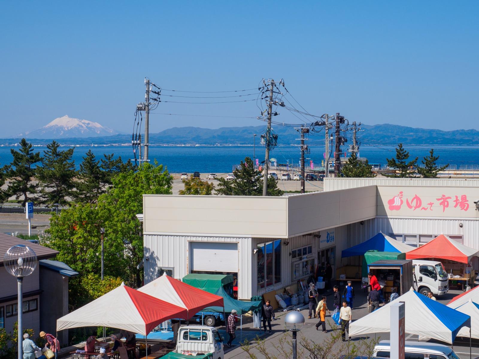 浅虫温泉駅前のゆうやけ橋から見える「道の駅浅虫温泉駅」の「ゆ〜さ市場」と、津軽半島の岩木山
