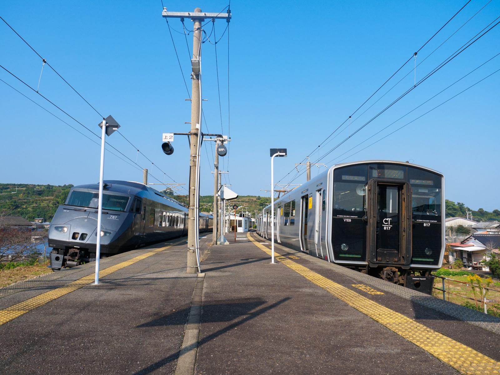 肥前飯田駅に停車する普通列車と、通過する特急「かもめ」