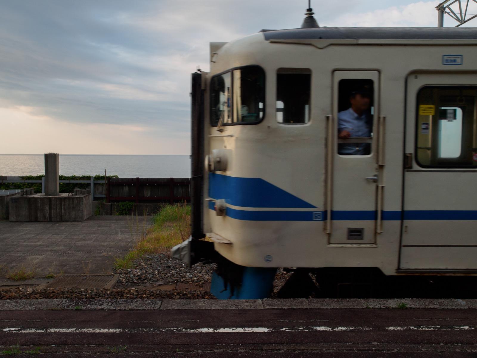 市振駅を発車する列車と日本海の水平線