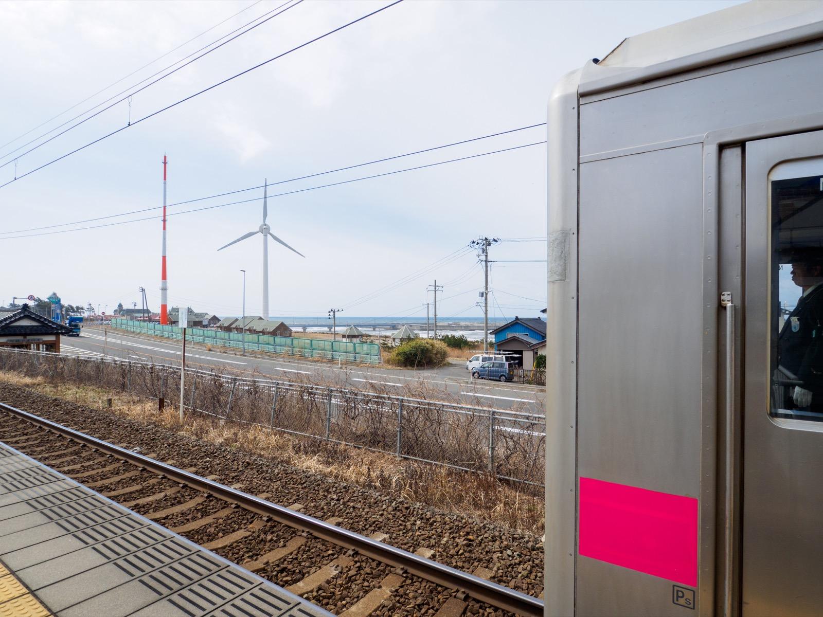 岩城みなと駅のホームから見た日本海と風車(2016年3月)
