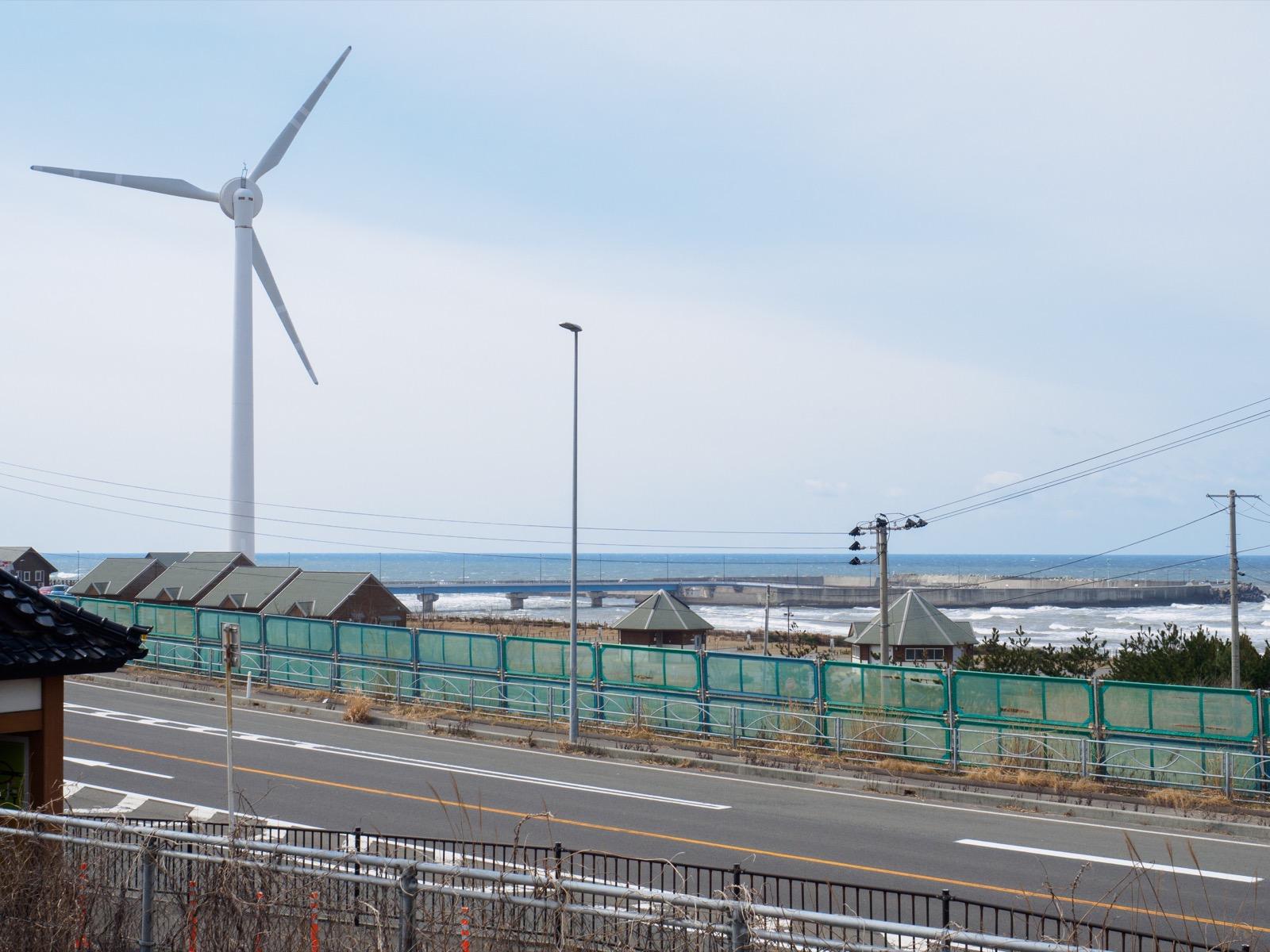 岩城みなと駅のホームから見た風車と道川漁港(2016年3月)