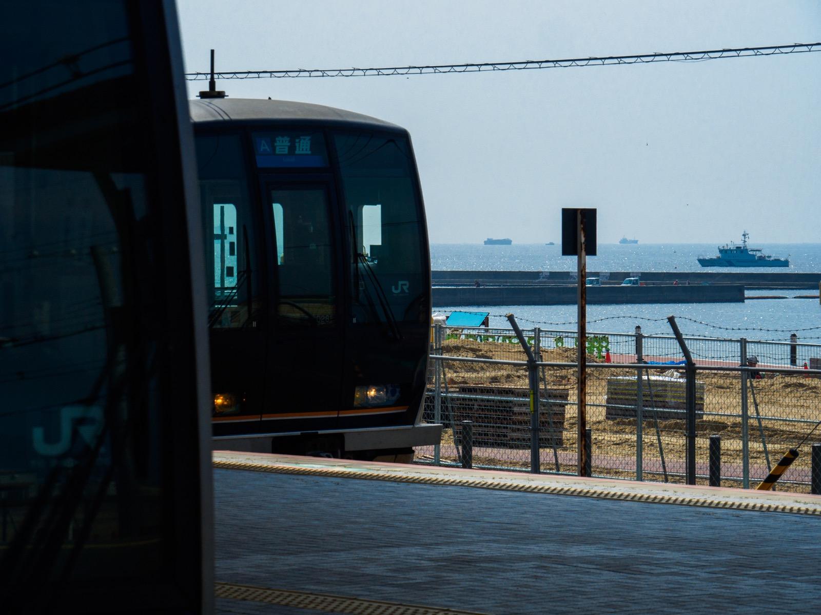 須磨駅に停車する列車と、大阪湾を行き交う船