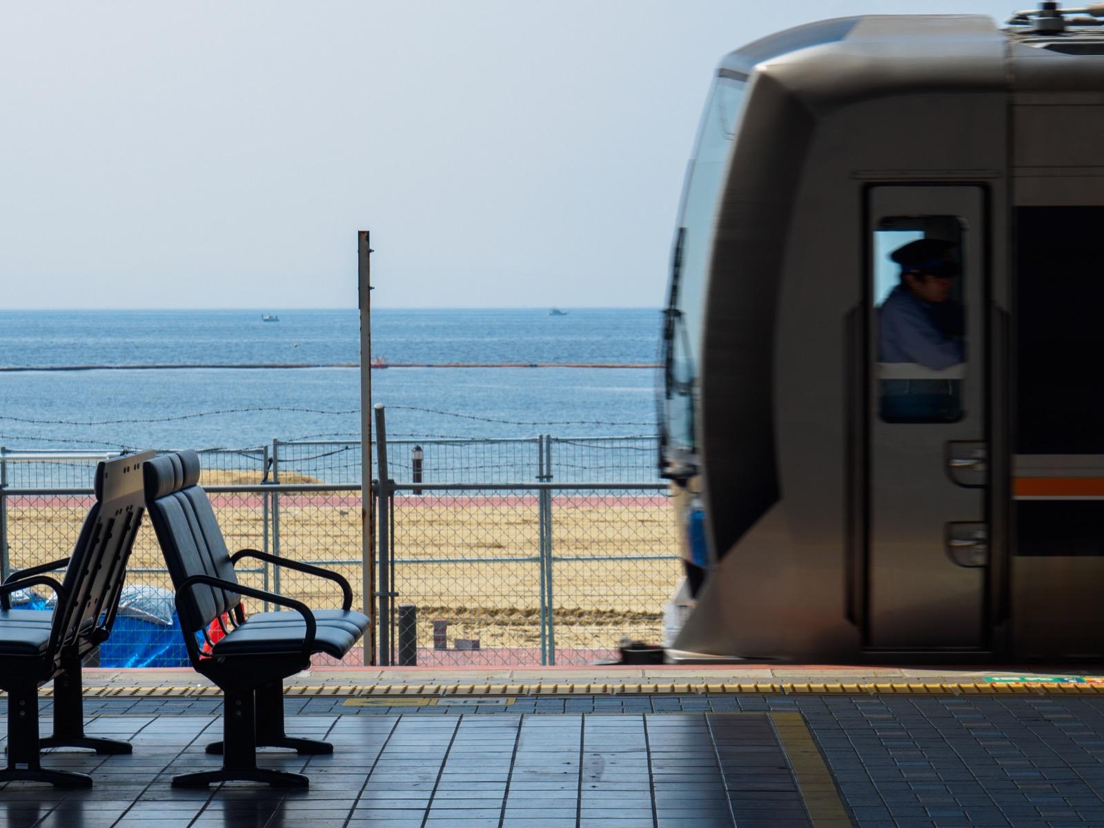 須磨駅を発つ列車と須磨海水浴場